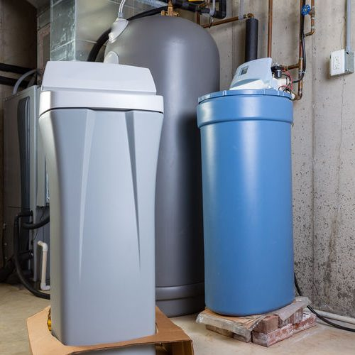 Old & New Water Softener Tanks In a Utility Room